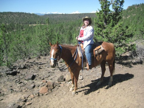 Nancy D. Brown on an Oregon horseback riding vacation with the Three Sisters mountains in the background.