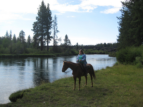 Nancy Brown riding Diesel on a horseback riding vacation along the Deschutes River
