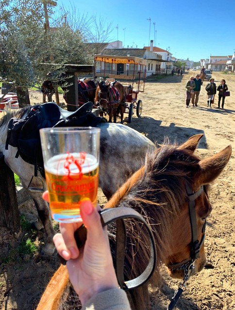 holding beer while horse riding in El Rocío