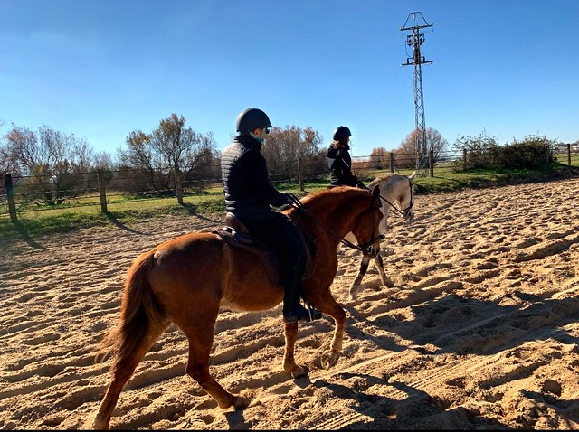 Two horse riders on sandy Raya Real toward El Rocio, Spain