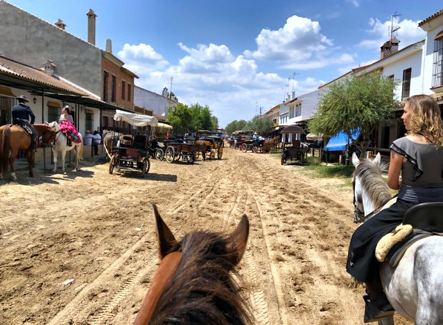 horses and riders, carriages on the sandy street of El Rocío, Spain
