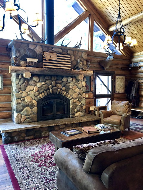 Deer and elk horns are mounted above the stone fireplace inside Taylor Fork Lodge at Covered Wagon Ranch, Montana