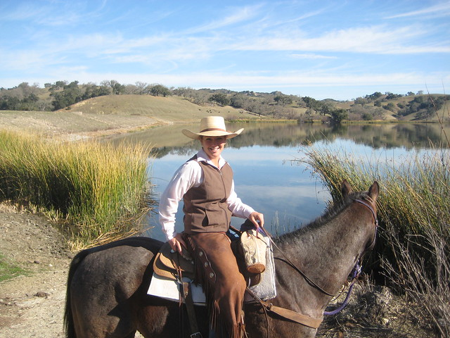 Wrangler Haddie Tal Townsend on her horse in front of the lake at Alisal Guest Ranch in Solvang, California