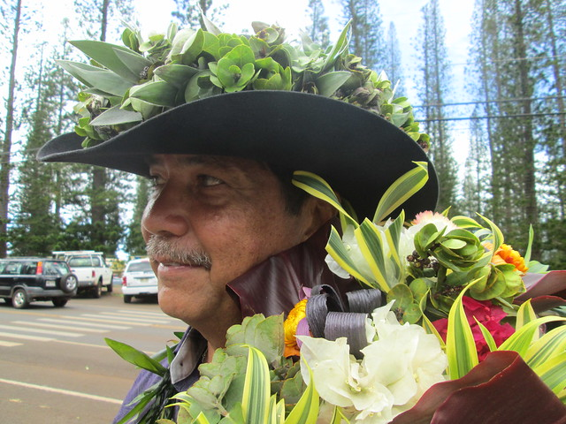Hawaiian cowboy from Maui wearing a cowboy hat with Hawaiian greens. Fresh flowers from Maui are on his shoulders.