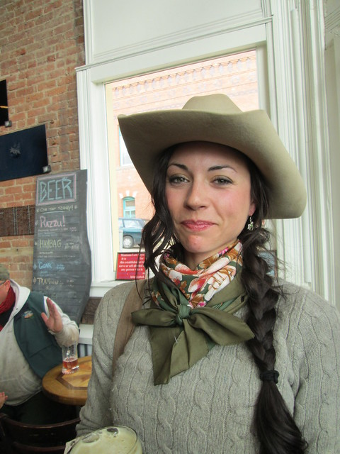 Rock Creek Ranch Wrangler with braids and scarf wearing her cowboy hat.