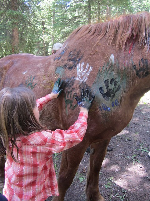 Young child places painted hand prints on horse during children's program at Lone Mountain Ranch in Montana.