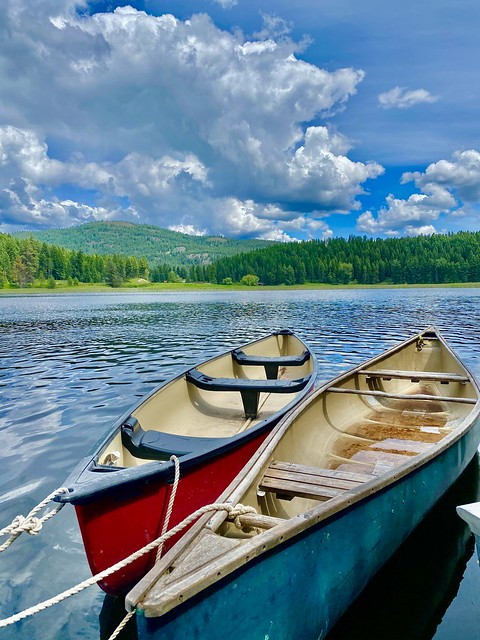 Two canoes float on Spencer Lake with Whitefish, Montana clouds in the distance.