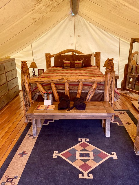 Montana glamping tent with queen bed, handcrafted log furniture, woven Western rug.
