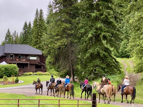 Horses and riders walk past Bar W Guest Ranch toward the stables after a trail ride in Whitefish, Montana.