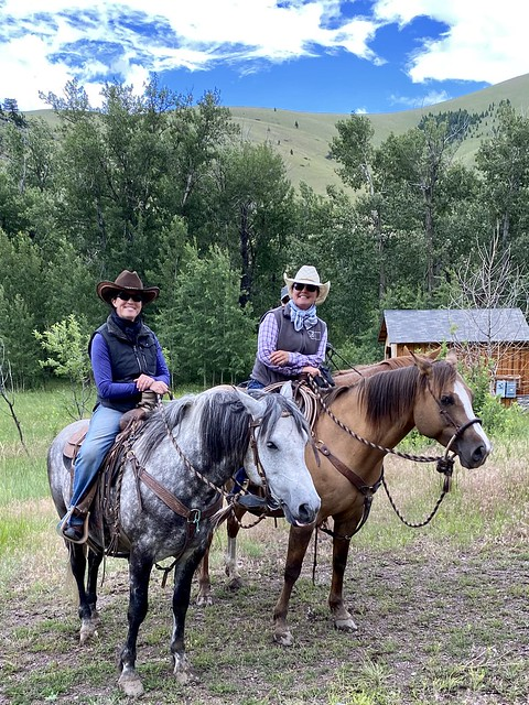 Cowgirls Anna and Maria Wirth sit on their horses, ready to take guests on a horse riding vacation near Helena, Montana.