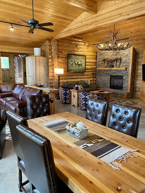 Elk log cabin interior with elk antler shed chandelier, dining room, leather sofa and rock fireplace.