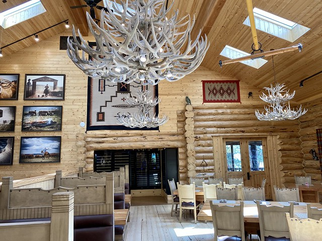 The dining room at Silvies Valley Ranch lodge includes restaurant booths and tables. Large elk shed chandeliers suspend from the wood-beamed ceiling in Seneca, Oregon.