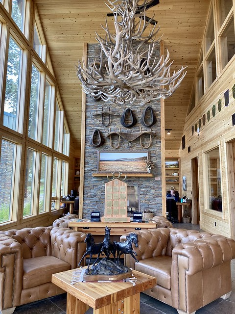 Rock fireplace decorated with horse wagon yokes, tan leather furniture and elk shed chandelier greet guests open arrival at Silvies Valley Ranch Gate House in Seneca, Oregon.